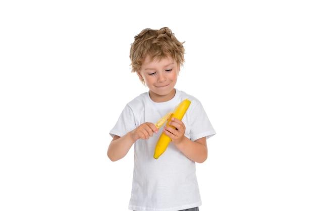 Il ragazzo sbuccia una banana gialla brillante con l'intento di mangiarla.