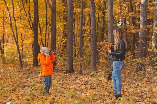 Ragazzo fotografo scatta foto di una madre nel parco in autunno hobby foto arte e tempo libero