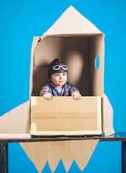Ragazzo gioca con il concetto di infanzia razzo bambino in cartone giocattolo razzo sogno d'infanzia astronauta