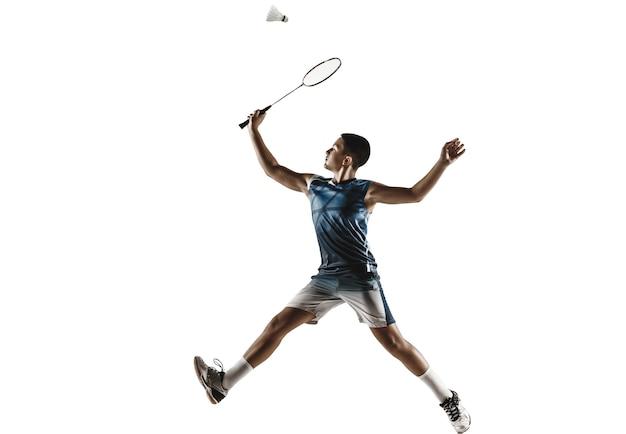 Ragazzo che gioca a badminton isolato sul muro bianco.