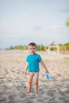 Ragazzo che gioca sulla spiaggia gioco da bambini in mare in estate vacanza in famiglia sabbia e giochi d'acqua protezione solare