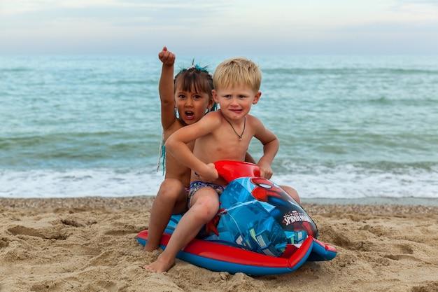 Un ragazzo che gioca sulla spiaggia con moto d'acqua gonfiabile per bambini ucraina mar nero