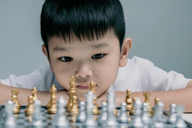Ragazzo che gioca a scacchiera, competizione negli affari,