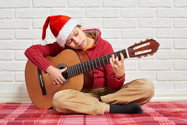 Ragazzo che suona la chitarra acustica di musica vestito con un maglione rosso e un cappello della santa
