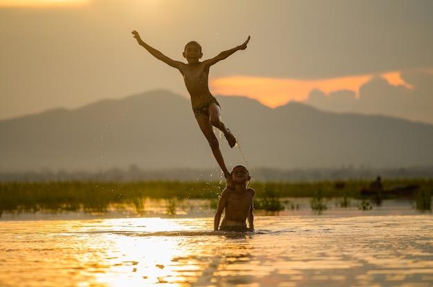 Ragazzo che gioca spruzzi d'acqua nel fiume durante il tramonto, spruzzi d'acqua, thailandia