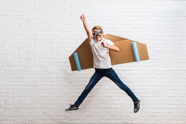 Ragazzo che gioca con le ali di aeroplano di cartone saltando