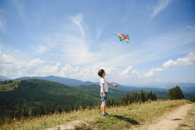 Ragazzo che gioca con un aquilone in montagna