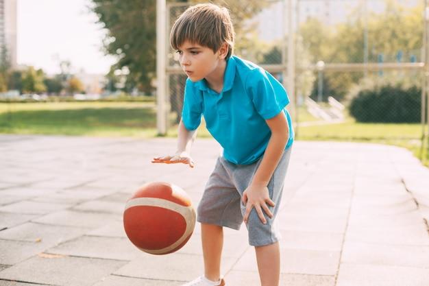 Un ragazzo gioca a basket dopo la scuola. sport, stile di vita sano, tempo libero