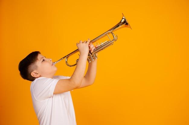 Un ragazzo suona la tromba. il bello ragazzo dell'adolescente gioca lo strumento musicale della tromba