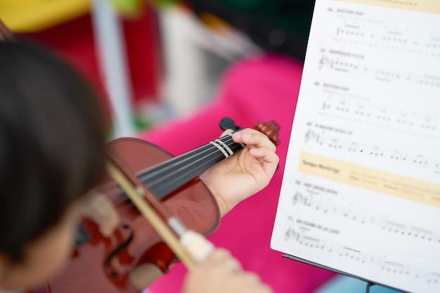 Il ragazzo gioca il violino con la corda dell'arco con lo spazio della copia sul fondo della sfuocatura, sul fuoco selettivo e sulla condizione della nota della sfuocatura