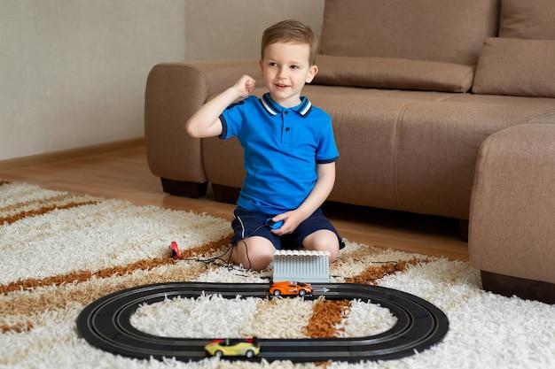 Il ragazzo gioca con la pista sul telecomando sul tappeto