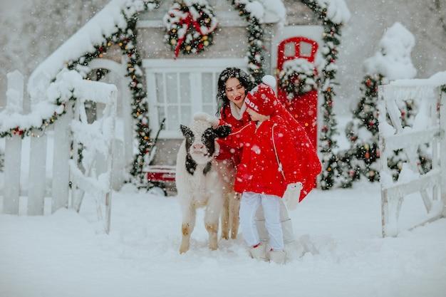 Ragazzo e bella donna in posa con piccolo toro al ranch invernale con decorazioni natalizie. nevicando.