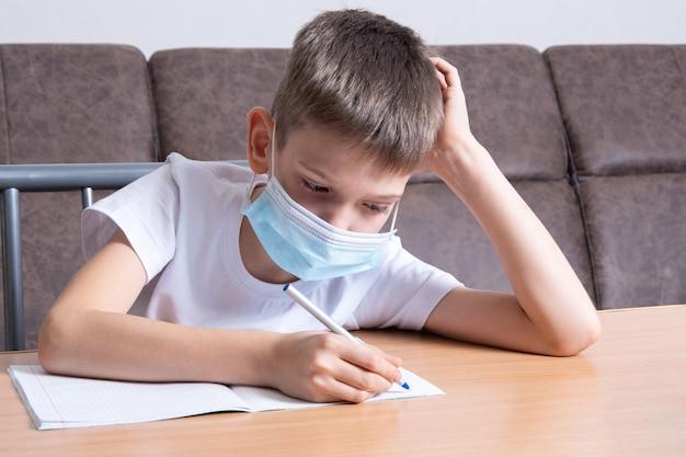 Un ragazzo con una maschera protettiva sul viso sta studiando online, scrivendo informazioni su un taccuino, seduto alla sua scrivania a casa. concetto di formazione online, apprendimento a distanza