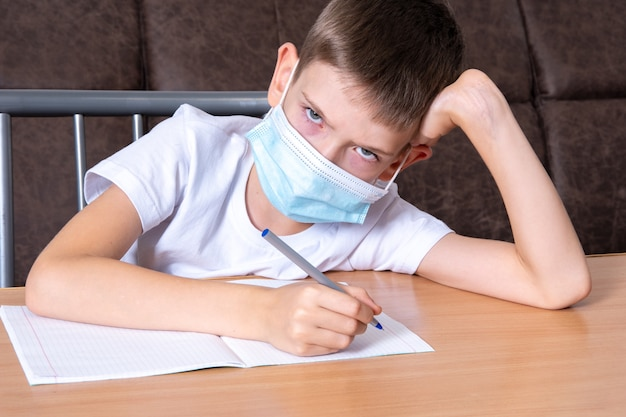 Un ragazzo con una maschera protettiva sul viso ti guarda con dispiacere, il bambino non vuole studiare online a casa. concetto di formazione online, apprendimento a distanza