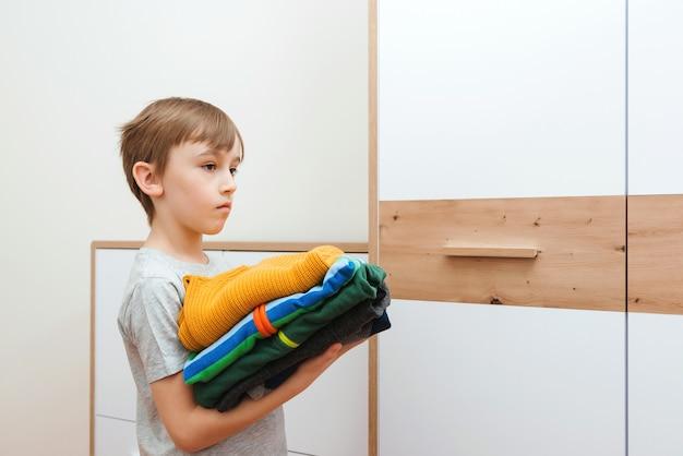 Il ragazzo mette le cose in ordine nell'armadio. una pila di vestiti colorati.