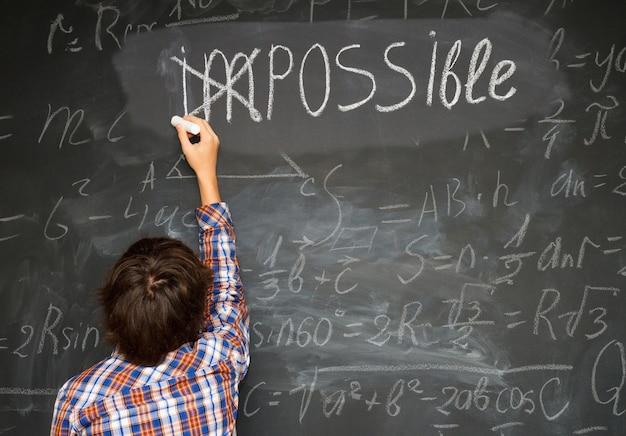 Ragazzo che mette un incrocio sopra impossibile sulla lavagna con calcoli di matematica