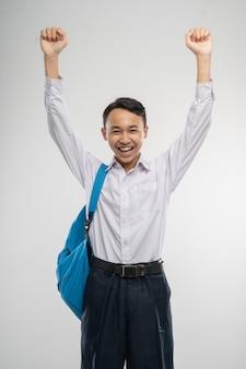 Un ragazzo ha alzato le mani in uniforme della scuola media sorridendo con la borsa della scuola