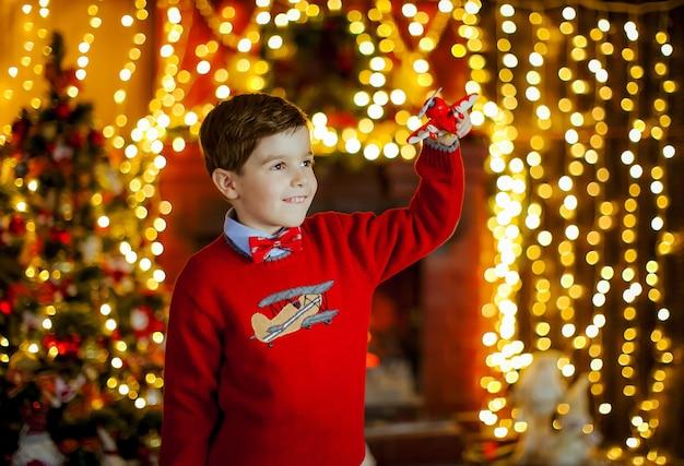 Ragazzo in un maglione rosso brillante tra le luci di natale
