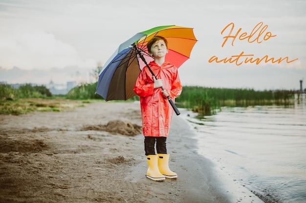 Un ragazzo con un impermeabile rosso e stivali di gomma gialli si trova sulla riva del fiume e tiene in mano un ombrello arcobaleno