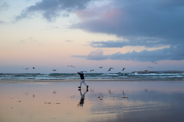 Ragazzo che corre con gli uccelli in inverno spiaggia vicino all'oceano