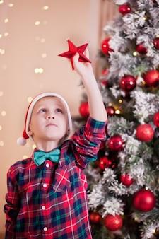 La mano del ragazzo che tiene una grande stella rossa della decorazione di natale in mani sui precedenti dell'albero di natale