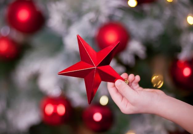 La mano del ragazzo che tiene una grande stella rossa della decorazione di natale in mani per l'albero di natale