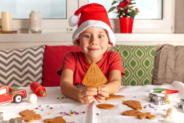 Un ragazzo con un cappello di babbo natale tiene in mano un biscotto allo zenzero a forma di albero di natale che cucina nuovi...