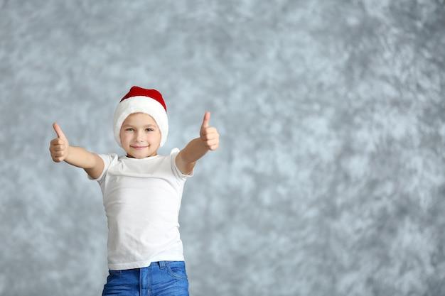 Ragazzo con cappello da babbo natale che gioca su sfondo grigio