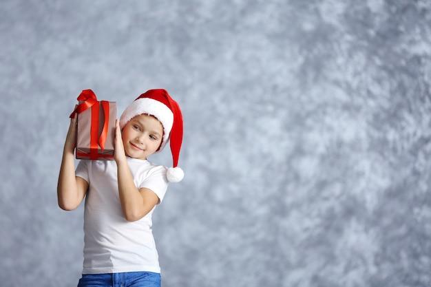 Ragazzo con cappello da babbo natale con scatola regalo su sfondo grigio