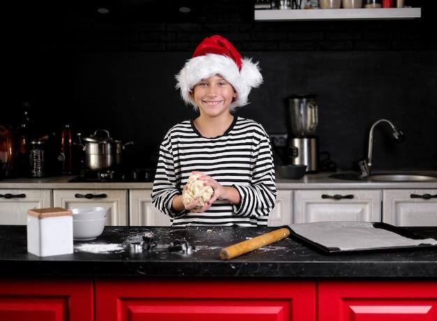 Il ragazzo con il cappello di babbo natale sta cuocendo una torta di natale in cucina. nei toni del nero, rosso e bianco