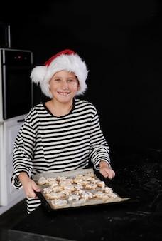 Il ragazzo con il cappello di babbo natale sta cuocendo una torta di natale in cucina e sorride. nei toni del nero, rosso e bianco