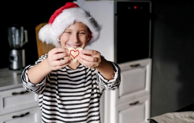 Il ragazzo con il cappello di babbo natale sta cuocendo una torta di cuore di natale in cucina e sorride.