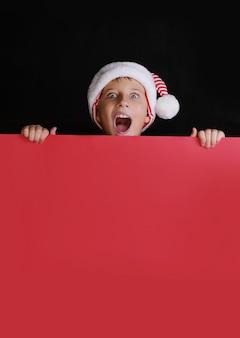 Ragazzo in cappello di babbo natale che grida e che tiene la carta bianca rossa per gli auguri di natale. isolato sul nero