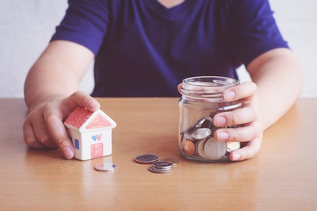 Ragazzo risparmiando soldi per l'acquisto di casa. piano per l'acquisto del concetto di casa.