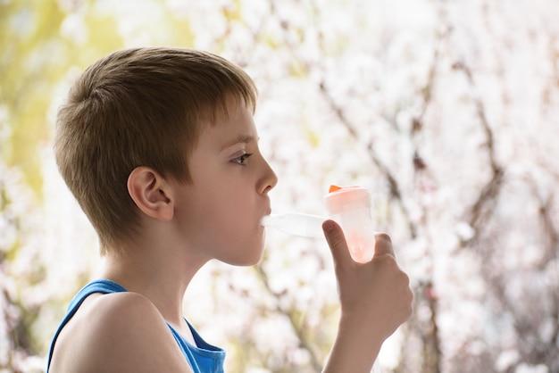 Ragazzo dell'età scolare nell'inalatore della maschera respiratoria su un fondo degli alberi di fioritura. trattamento domiciliare. prevenzione