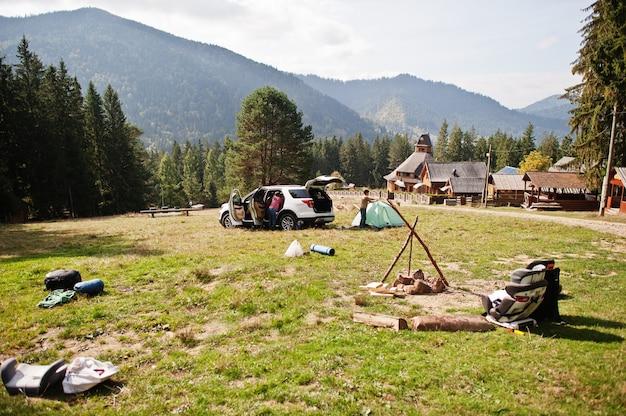 Il ragazzo monta una tenda. viaggiare in auto in montagna, concetto di atmosfera.