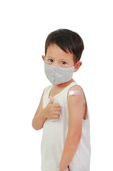 Ragazzo che mostra braccio con cerotto adesivo, cotone da vaccinato. ragazzino asiatico babay con gesso sulla spalla dall'iniezione. trattamento del cerotto per bambini. concetto di vaccinazione