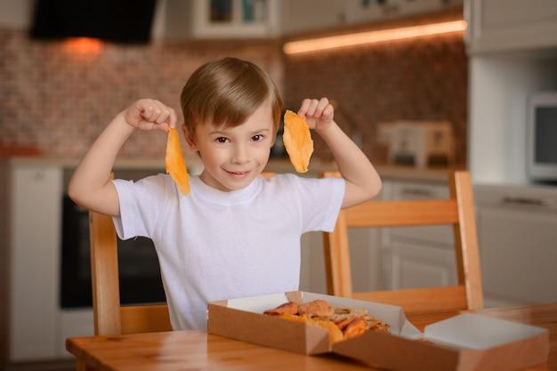 Il ragazzo mostra mango essiccato, che ha estratto dalla scatola con frutta secca Foto Premium