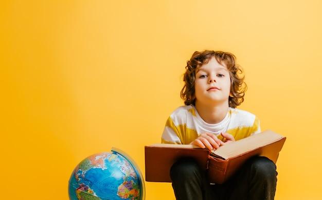 Ragazzo si siede su una pila di libri, vicino al globo