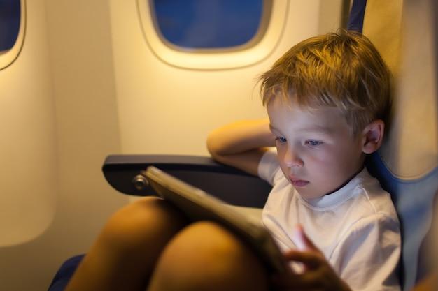 Ragazzo che si siede nell'aereo e che utilizza il tablet pc