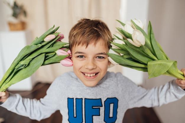 Il ragazzo sorride con fervore con un mazzo di fiori
