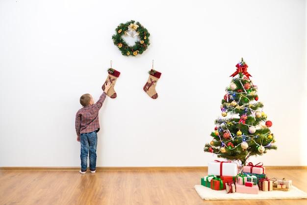 Il ragazzo sta vicino alla decorazione natalizia sul muro