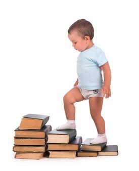 Il ragazzo sta su una pila di libri per un ritratto educativo - isolato su una superficie bianca