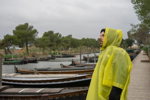 Ragazzo in una giornata tempestosa con un impermeabile. foto scattata al porto di catarroja a valencia, in spagna.