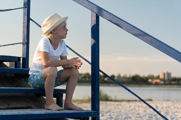 Ragazzo in cappello di paglia che si siede sulle scale in spiaggia