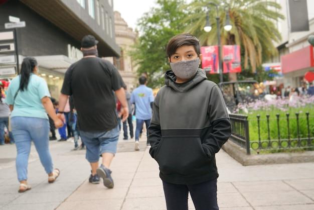 Ragazzo in strada con una maschera