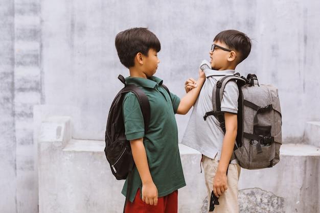 Studente ragazzo vittima di bullismo a scuola o bambini che litigano o attaccano il loro compagno di classe a scuola