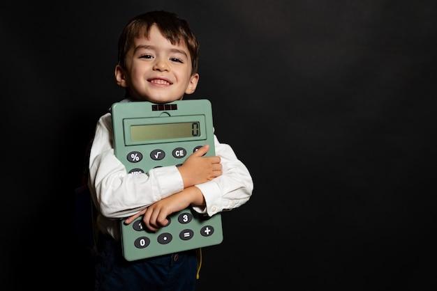 Ragazzo studente con zaino e calcolatrice in mano su sfondo nero