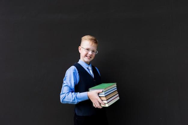 Lo studente ragazzo con un libro su sfondo nero