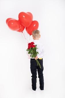 Il ragazzo in tuta tiene il mazzo di rose e palloncini a forma di cuore, sta con le spalle a un muro bianco.